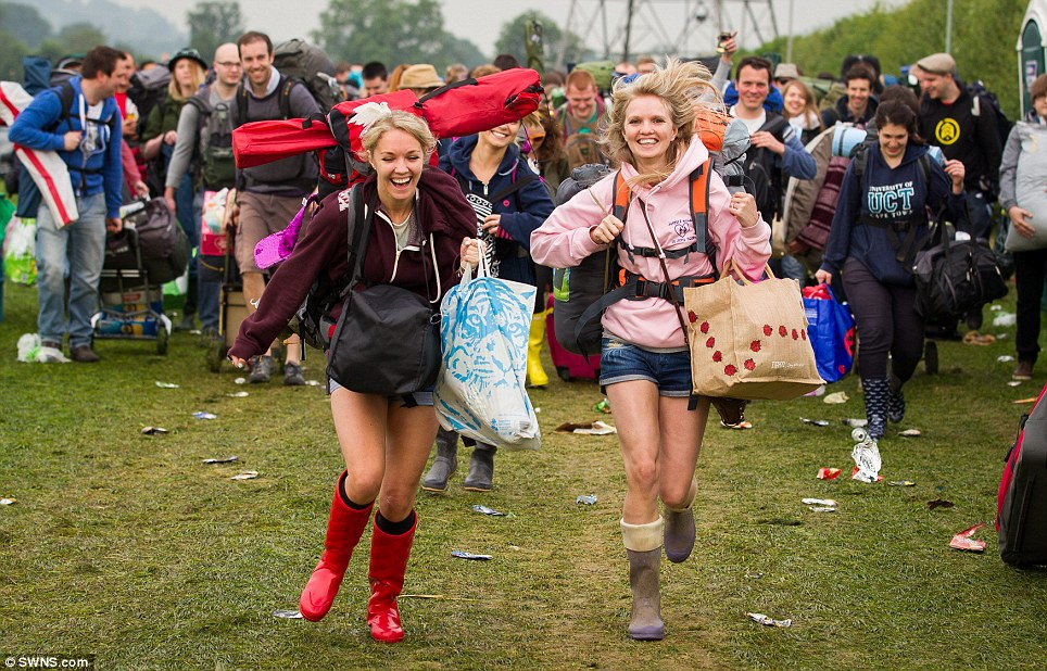 Jenny Twiss, 31, and Genna Mann, 27, ran to the entrance at the start of Glastonbury Festival at Pilton in Somerset today - sensibly, they had brought their wellies