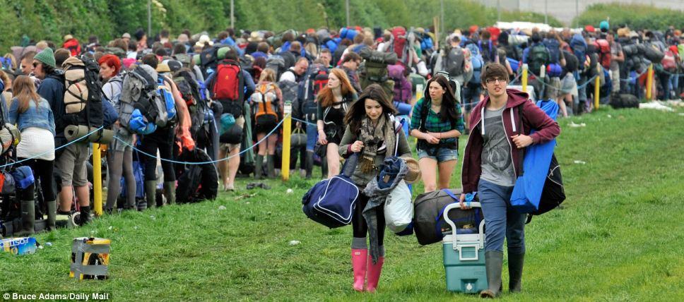 Standing out from the crowd: These youngsters drag their festival gear across the grass having waited their turn in the queue and finally made it onto the festival site