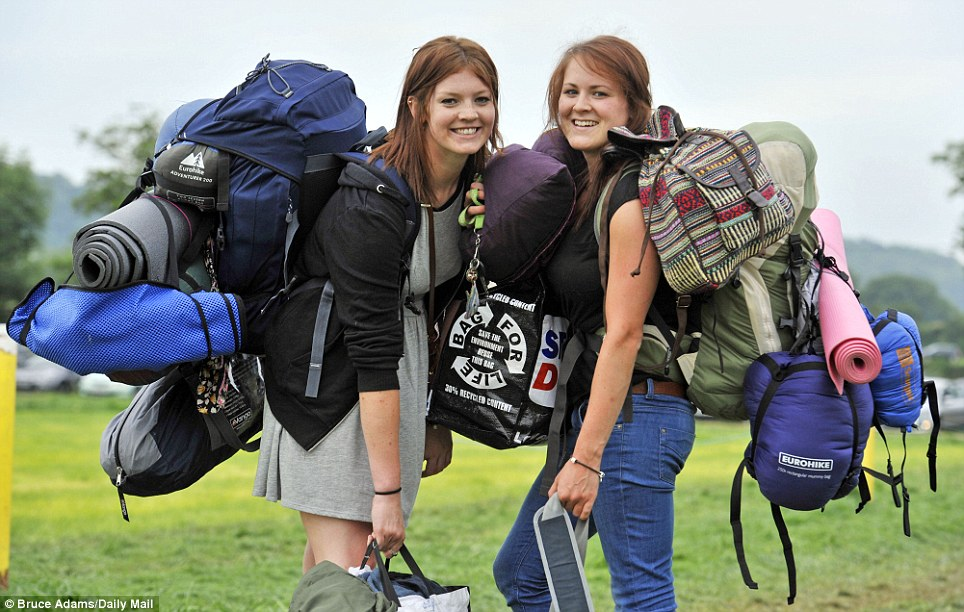Everything but the kitchen sink: Millie Jellie, 20, and her friend Katie Abbott, 22, from Bristol, were laden down like pack-horses as they queued to get into Glastonbury this morning