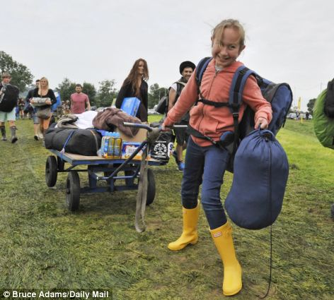 This youngster struggles to pull her belongings to the Glastonbury campsite earlier