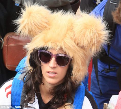 A festival goer sports some unusual headgear as she arrives at Glastonbury today