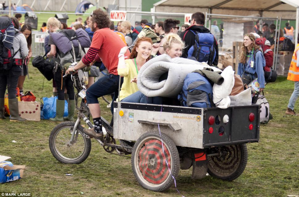 Hitching a ride: These two girls find a novel way of reaching the campsite as they are given a lift on a trailer