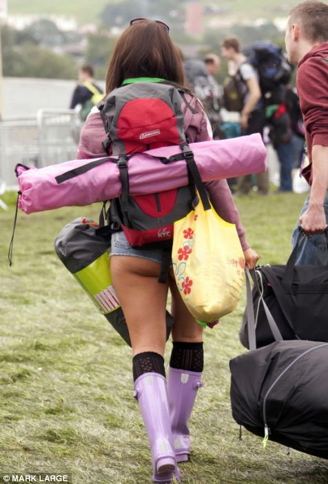 One festival goer makes the most of the warm weather by wearing tiny shorts as she carries her tent ready to pitch it at Glastonbury