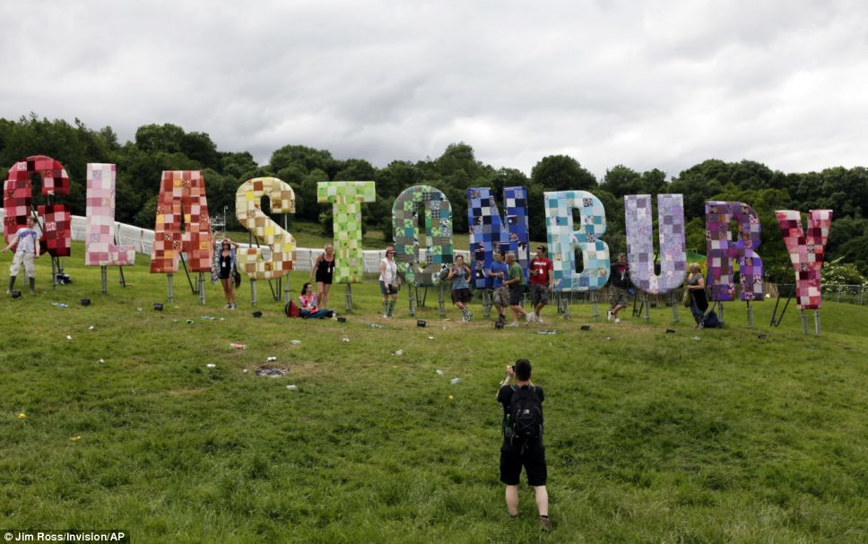 One for Facebook: Festival goers pose in front of a colourful Glastonbury sign which adorns part of the festival site