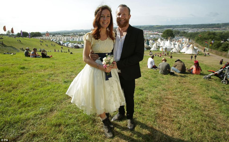 Just married: Newly-wed festival goers John and Mathilda Fristrom Eldridge, from Newquay, enjoy taking their honeymoon at the Glastonbury Festival