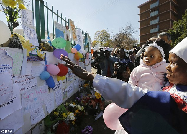 Tributes: A woman and her young child look at prayers left by well-wishers outside the hospital