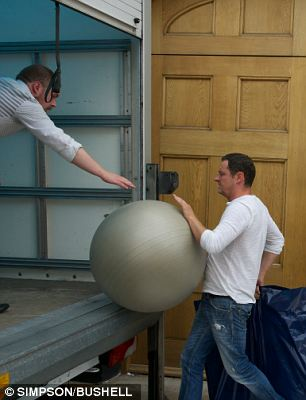 A removal man loads an inflatable exercise ball into the van outside the Saatchi home in Chelsea