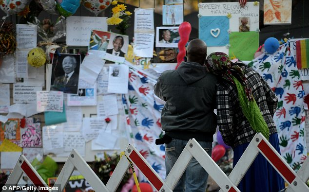Admiration: Two people look at the tributes to Mr Mandela left outside the hospital where he is being treated