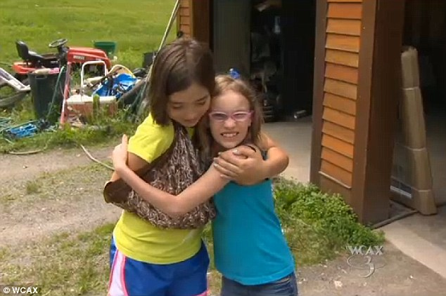 Best friends: Irie Campbell, right, her arm still in a sling, hugs Piper Rolfe after 10-year-old Piper helped fend off a vicious raccoon
