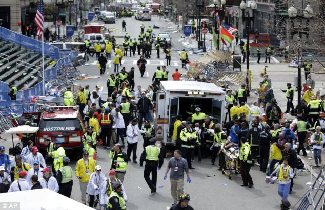 Devastation: Medical workers rush to help the injured at the finish line of the Boston Marathon after two pressure cooker bombs were detonated near the finish line on April 15