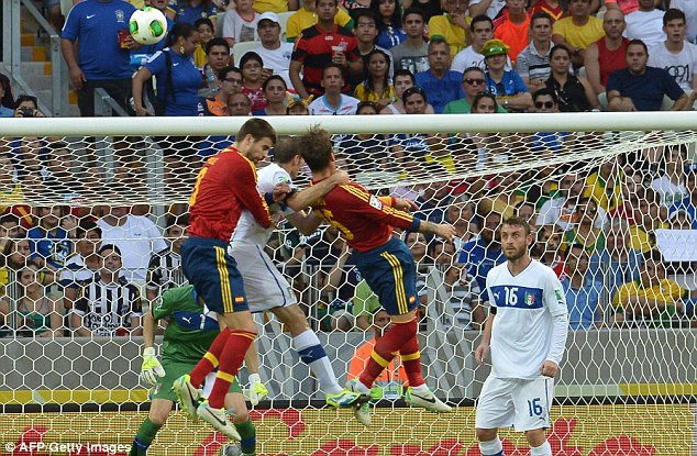 Defending giant: Pique and Sergio Ramos leapt into the air in an attempt to defend a goal during the match in Fortaleza