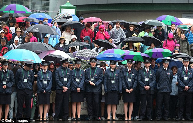 March of the brollies: Spectators and stewards take shelter in any way they can from the pouring rain as the gates open at Wimbledon