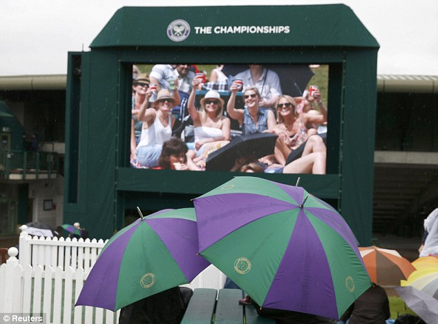 Hope: Spectators sit underneath their umbrellas on Henman Hill as they watch a replay of Andy Murray's last round match on the big screen