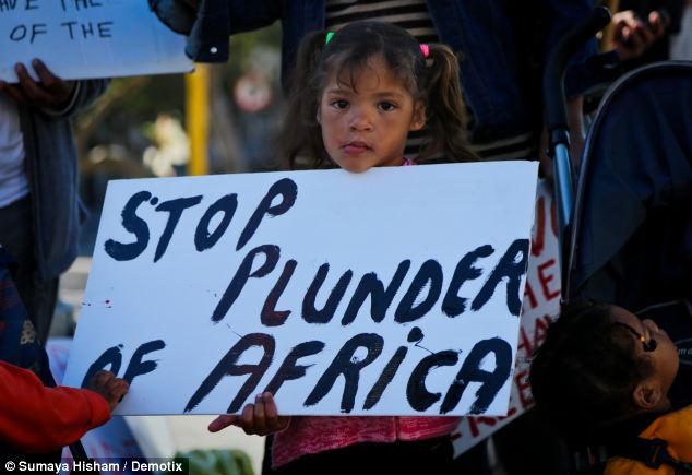 Outside the Parliament building in Cape Town a young girl held up a placard reading: 'Stop plunder of Africa'