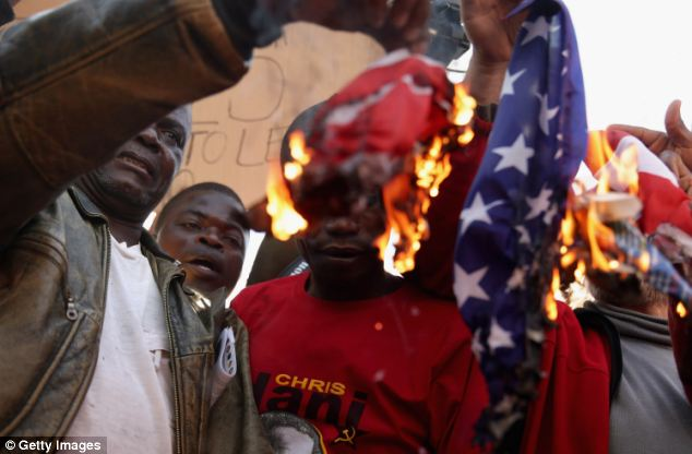 About 800 people marched through Pretoria to voice their opposition to Obama and U.S. policy in South Africa and around the world, while some demonstrators burned an American flag