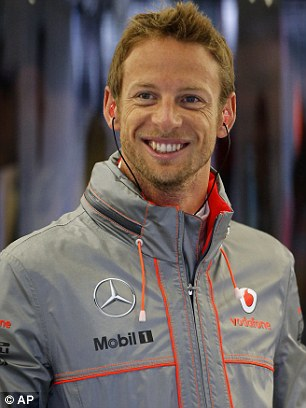 Positive: Button is confident of a much higher finish this Sunday, and was all smiles during a damp P1