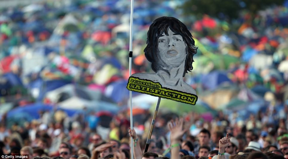 Fans wave a painted cut out of Mick Jagger above the crowd which reads 'I can't glasto satisfaction'