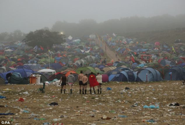 A group of festival-goers, including one dressed as superman, makes their way through the rubbish back to their tents as dawn breaks