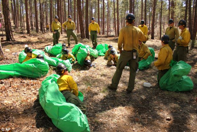 Elite team: A photo from April 12, 2012 shows a squad leader with the Granite Mountain Hotshots training crew members on setting up emergency fire shelters outside of Prescott, Arizona