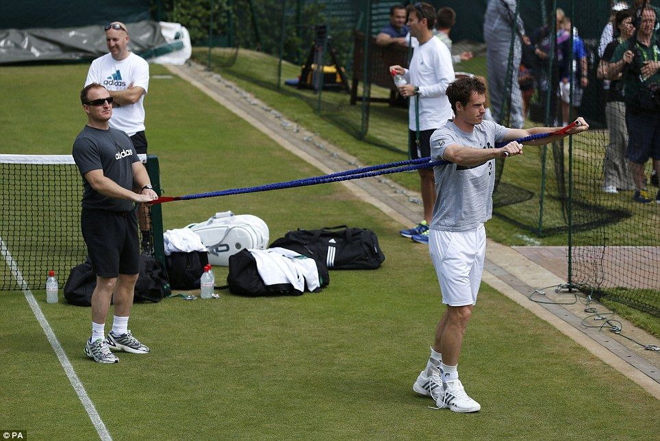 Flexing his muscles: Andy Murray stretches during a practice session ahead of his fourth-round tie against Russia's Mikhail Youzhny on Centre Court today