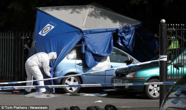 Police cover a blue car in a forensic tent to gather evidence that could help in their hunt for the attacker