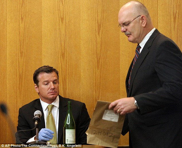 Artifacts: State's Attorney John Smriga presents evidence, a sake bottle, to Bridgeport Police Lt. Christopher LaMaine who was the first witness to give evidence in the trial