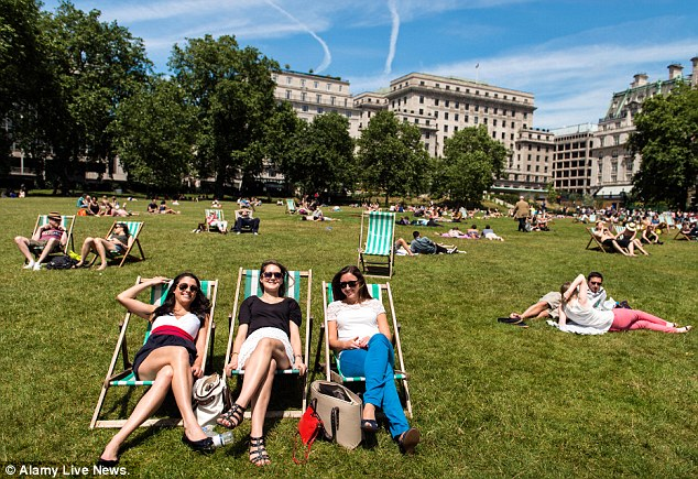 People sunbathing in Green Park today. Forecasters say that the hot weather is here to stay until August