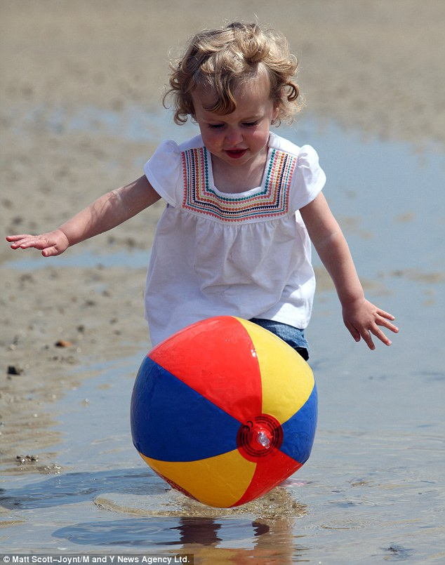 Hannah Travers, 2, tries to catch a beach ball as she plays on the beach with her family