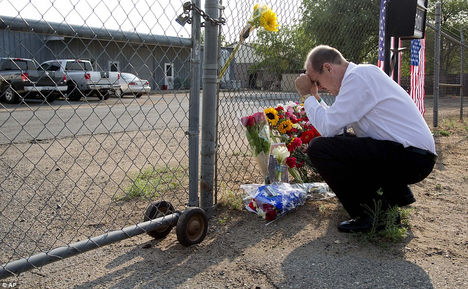 Overwhelmed: Local resident Bob Hoskovec says a prayer as he kneels outside the gate on Monday