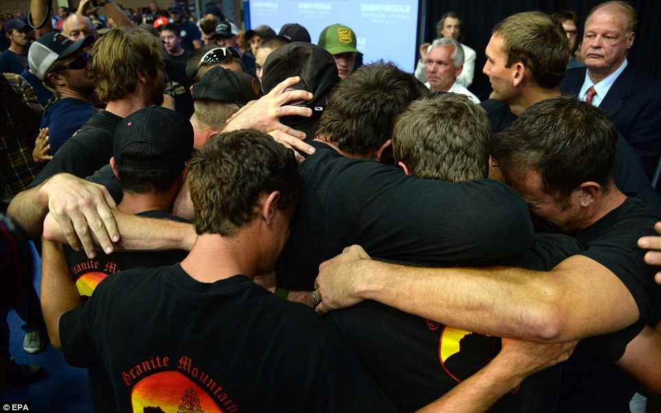 Hugs: Members of the Granite Mountain Emergency Hot Shot Crew hug each other during a memorial service at Embry-Riddle Aeronautical University in Prescott, Arizona