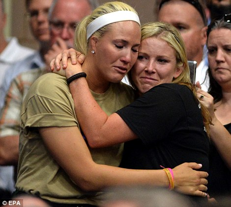 Support: Firefighters Kayla Garst and Darcee Knight hug each other, left, at Embry-Riddle Aeronautical University in Prescott, Arizona