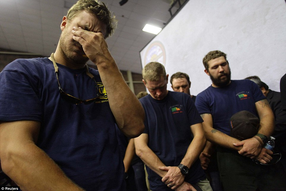 In mourning: Hotshot firefighters mourn during a moment of silence for the 19 firefighters who perished battling a fast-moving wildland fire at a memorial service