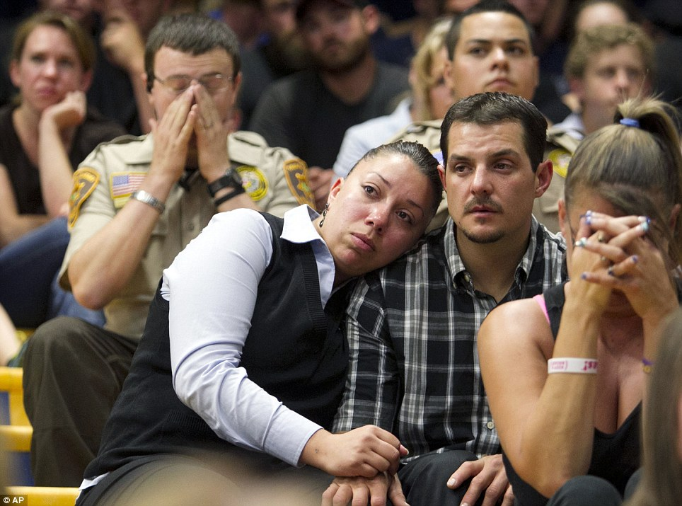 Overcome: Gina Martinez, center, and Chase Madrid, center right, comfort each other during a memorial service on Monday evening