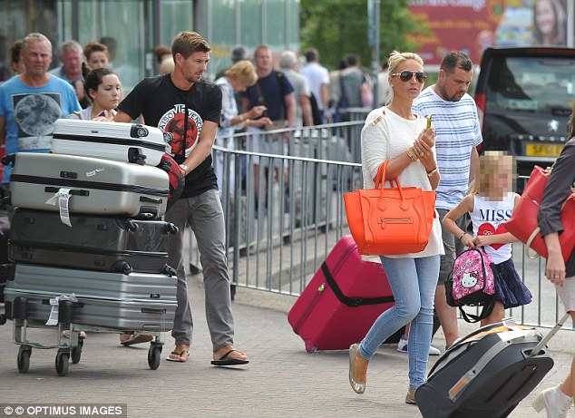 Packing his bags: Gerrard pushes the trolly with his families luggage on