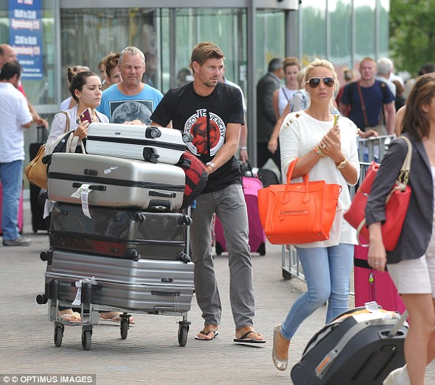 Home sweet home: Steven Gerrard and wife Alex return home from from holiday