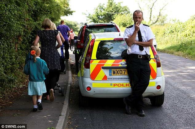Protection: A policeman stands guard while children walk to St Peter's Anglican Methodist Primary School