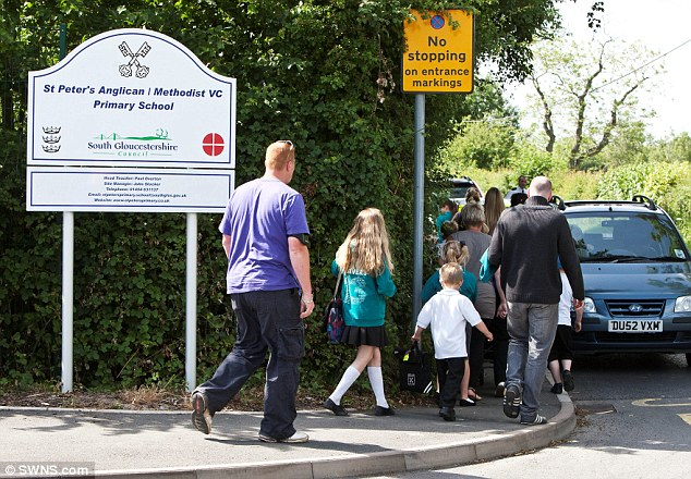 Concerns: Parents walk their children to the Gloucestershire school after travellers moved into their village