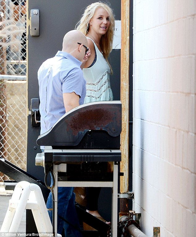 Good spirits: Britney smiled and looked happy and relaxed as she made her way into the studio