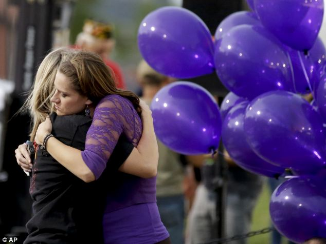 United in grief: Family members hug as they attend the community event