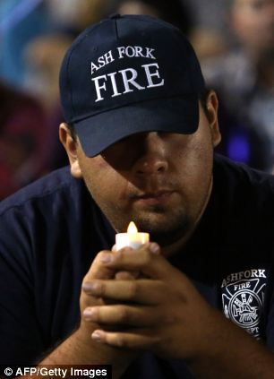 Firefighter Jesus Acosta holds a candle