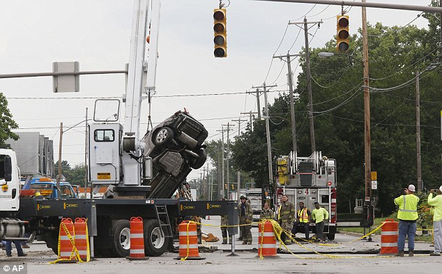 Recovery: The principal's Chevy Malibu is eventually recovered from the sinkhole using a giant crane