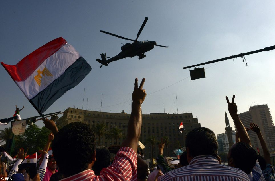 Egyptians flash the victory sign and wave Egypt's flags as an army helicopter flies by, one day after the announcement of a presidential handover