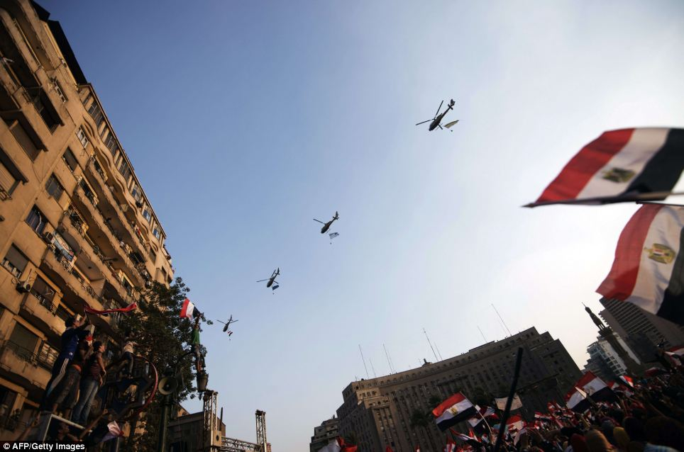 High above: The national flag is waved by the protestors as army helicopters fly above Tahrir Square