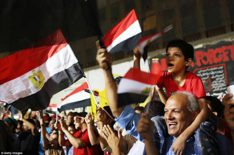 Celebration: Meanwhile, people continue to dance and cheer in Tahrir Square, following the ousting of Mohammed Morsi