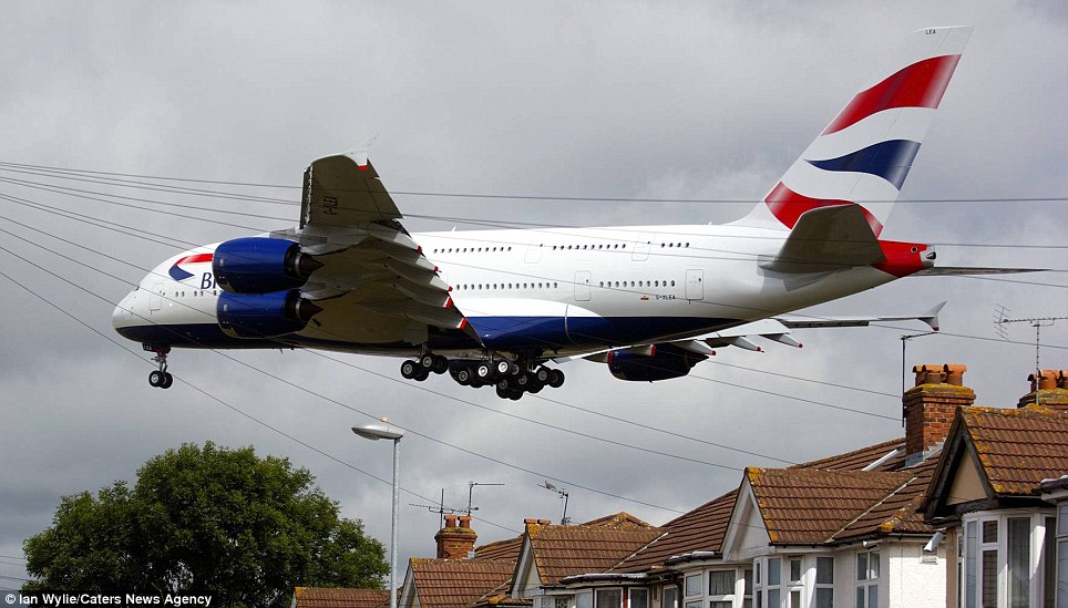 Homecoming: The Airbus A380 resplendent in distinctive BA livery dwarfs houses as it comes into land at Heathrow Airport, London
