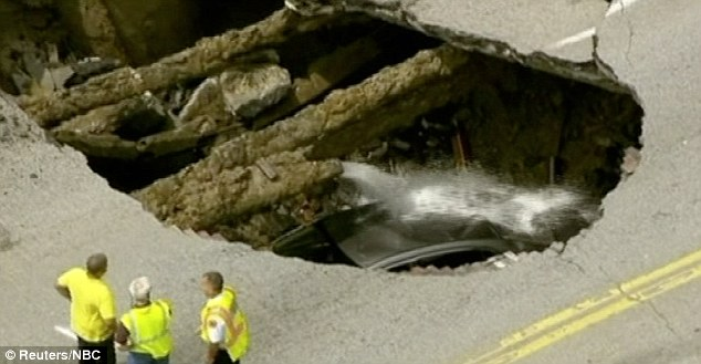 Ordeal: The swallowed up car was sprayed with water from a broken mains pipe, a possible cause of the sink hole