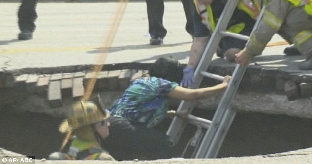 Shaky: Shocked Pamela Knox was helped up the ladder by firefighters after her terrifying ordeal