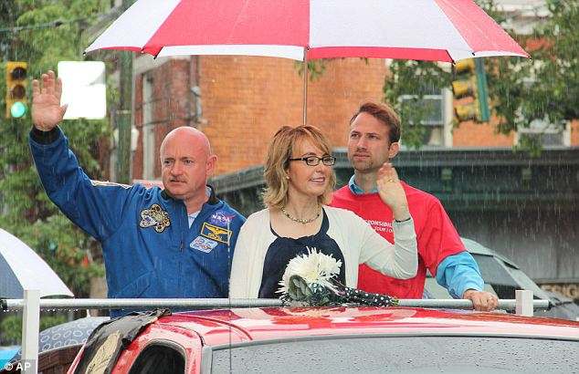 Famous faces: Former Congresswoman Gabrielle Giffords and her husband astronaut Mark Kelly are guests of honor at a Cincinnati Fourth of July parade