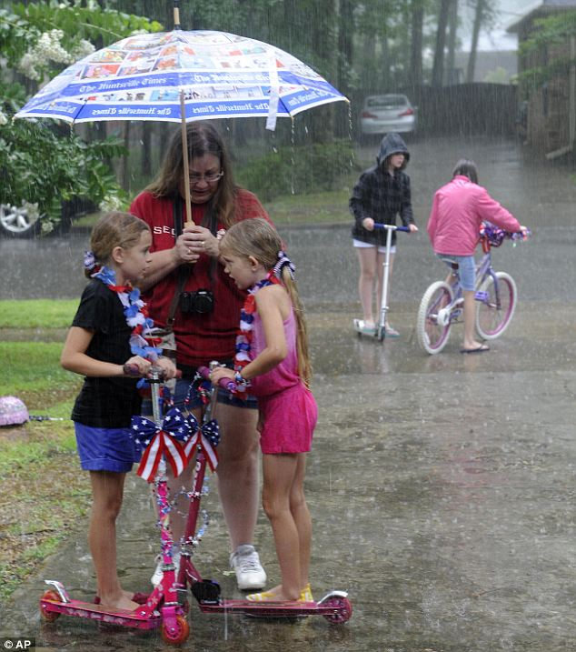 Wrecked by weather: A mother shields her daughter and her friend from the rain that was due to hit much of the south eastern United States throughout the day