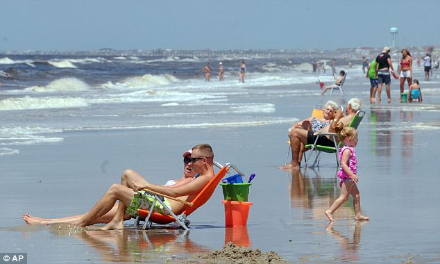 Hitting the beach: Visitors to Oak Island in North Carolina had a more relaxed approach to the holiday